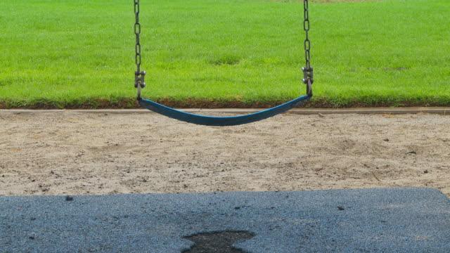 vídeos de stock e filmes b-roll de empty swing rocking in the breeze - equipamento de parque infantil