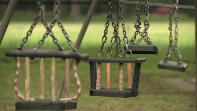 empty swings dangle at a park playground. - playground stock videos & royalty-free footage
