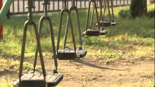 empty swings dangle in  an empty playground. - 遊具点の映像素材/bロール