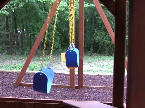 vídeos de stock, filmes e b-roll de vazio balanços em um playground 3 pal - grupo pequeno de objetos
