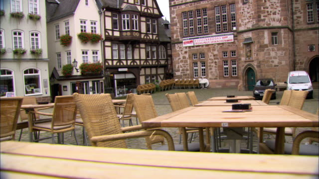 ms empty tables and chairs outside cafe in open square / marburg, germany - städtischer platz stock-videos und b-roll-filmmaterial