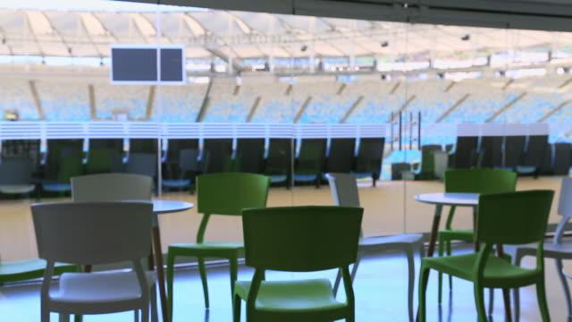 empty tables and chairs with empty maracana stadium behind - 講堂点の映像素材/bロール