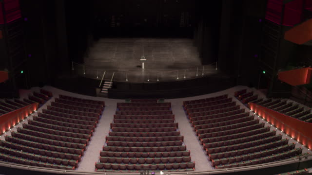 empty theatre with camera zooming down the centre onto stage. - bühne stock-videos und b-roll-filmmaterial