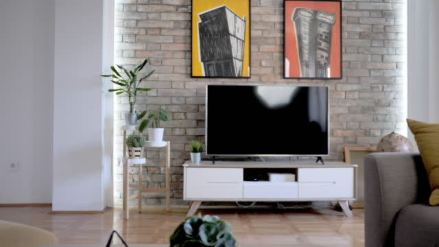 empty tidy living room with sofa and paintings on the walls - tidy room stock videos & royalty-free footage