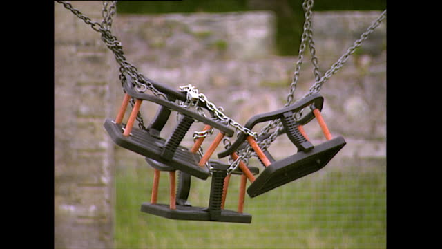empty toddler swings chained up and swaying; 1993 - 1993 stock videos & royalty-free footage