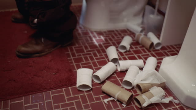 stockvideo's en b-roll-footage met cu empty toilet paper rolls on floor next to person sitting on toilet/ port washington, new york - afhankelijkheid