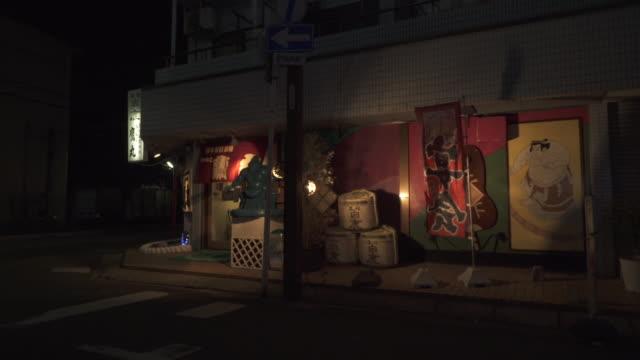 stockvideo's en b-roll-footage met empty tokyo street at night, restaurant on corner, wide shot - worstelen