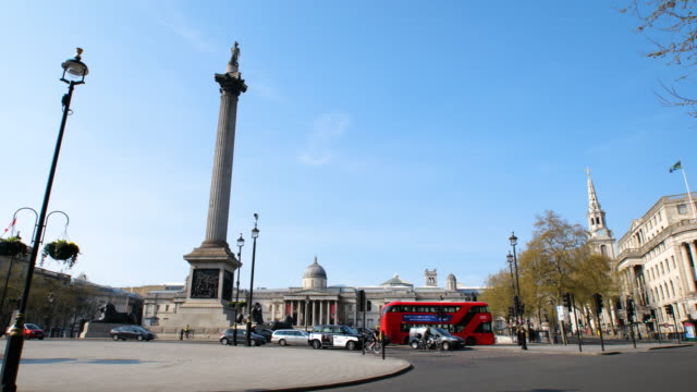 empty trafalgar square, entrance to charing cross underground station, red buses and car traffic passing during lockdown for coronavirus pandemic in... - famous place stock videos & royalty-free footage