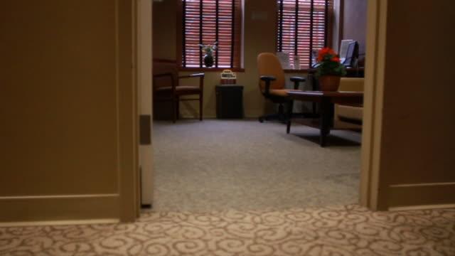 empty waiting room w/ windows coffee table chairs flowers doorway hallway carpet fg - coffee table stock videos & royalty-free footage