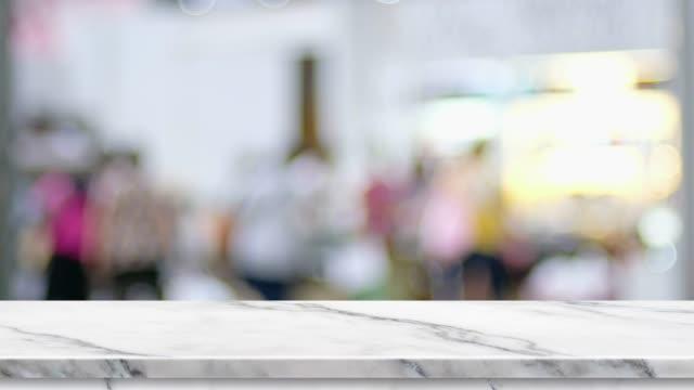 leere weiße marmor-tischplatte mit blur kunde einkaufen bei fachmesse mit hellem hintergrund bokeh, backdrop vorlage für die anzeige von produkt oder design, food-stand mock-up. - bartresen stock-videos und b-roll-filmmaterial