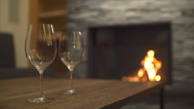 vídeos de stock e filmes b-roll de empty wine glasses and a fireplace in a restaurant at a luxury resort. - copo vazio