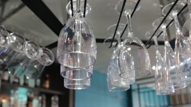vídeos de stock e filmes b-roll de empty wine glasses hanging on a rack - copo vazio