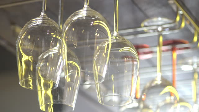 empty wine glasses hanging on a rack - dining stock videos & royalty-free footage