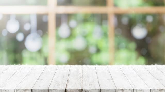 stockvideo's en b-roll-footage met leeg houten tafelblad op onscherpte met bokeh kerstboom en nieuwe jaar decoratie op raam banner achtergrond met sneeuwval - kan worden gebruikt voor het weergeven of monteren van uw producten.4k slow motion. - diavoorstelling