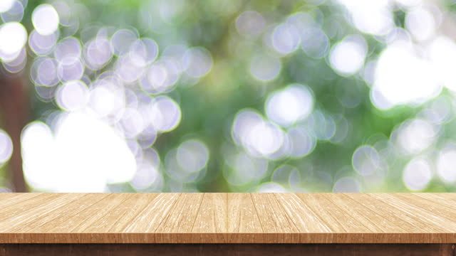 empty wood table top with blur green tree at park bokeh light background,backdrop template for display of product or design,food stand mock up - table stock videos & royalty-free footage