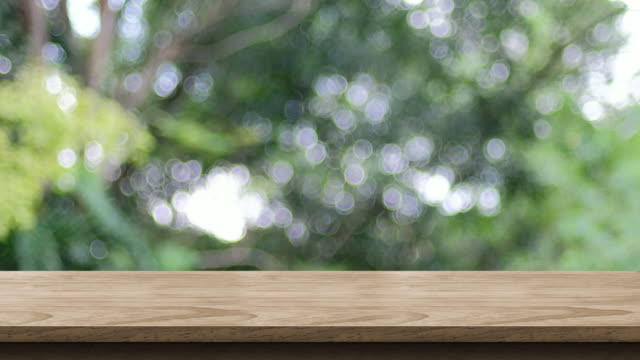 empty wood table top with blur green tree at park bokeh light background,backdrop template for display of product or design,food stand mock up - formal garden stock videos & royalty-free footage