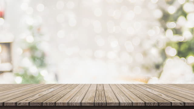 vídeos de stock e filmes b-roll de empty wooden table top with abstract warm living room decor with christmas tree string light blur background with snow,holiday backdrop for display of advertise product - visão frontal