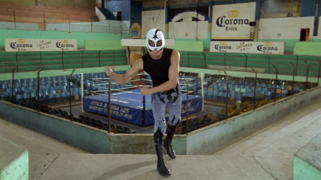 Empty wrestling ring/ luchador 'Cometa Negro' jumping onto balcony and flexing muscles at CAM/ Mexico