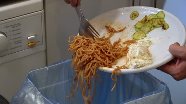 emptying pasta leftovers into rubbish bin. - food stock videos & royalty-free footage