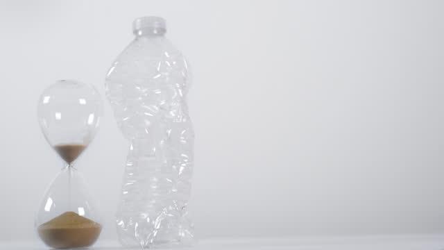 vídeos de stock e filmes b-roll de emptying sand timer next to plastic bottle - utilização única
