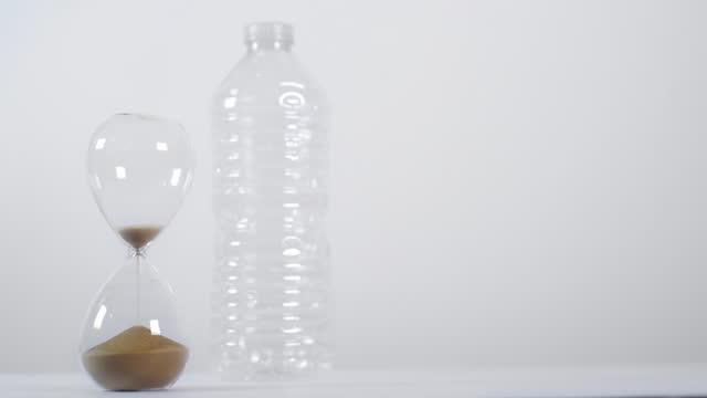 vídeos de stock e filmes b-roll de emptying sand timer with plastic bottle - utilização única