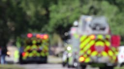 ems and fire truck at accident scene-intentionally blurred and with heat distortion from road