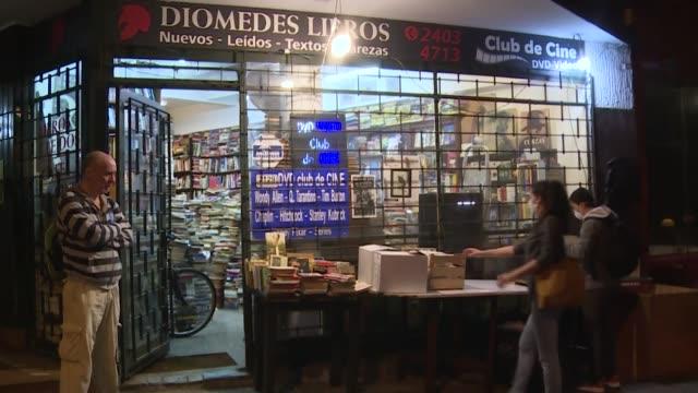 en el suelo por las paredes y hasta el techo el pequeño local de la librería está atiborrado de ediciones de distintas épocas tamaños y colores - comida stock videos & royalty-free footage