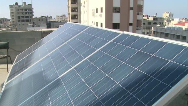 en el tejado del hospital infantil de gaza una improvisada hilera de paneles solares brilla por la luz del sol proporcionando una energía limpia un... - moderno stock videos & royalty-free footage