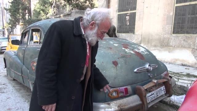 en la devastada ciudad siria de alepo abu omar cuida a diario con mimo su coleccion de coches antiguos haga sol llueva o caigan bombas - diario stock videos and b-roll footage