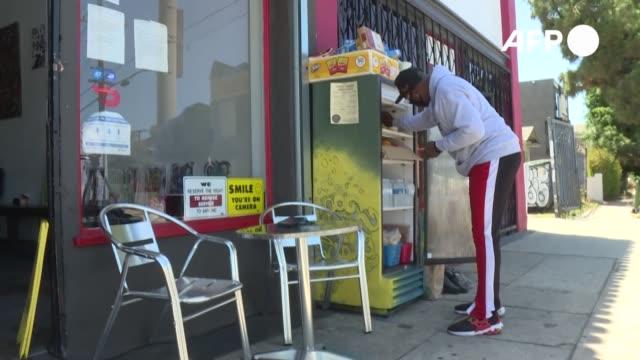 en medio de una acera solitaria de los ángeles un refrigerador rojo llama la atención con un letrero de comida gratis - comida stock videos & royalty-free footage