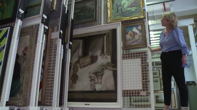 en un banal almacen de una calle del centro de londres se guardan miles de cuadros grabados y dibujos que esperan a ser distribuidos por todo el... - reino unido stock videos & royalty-free footage