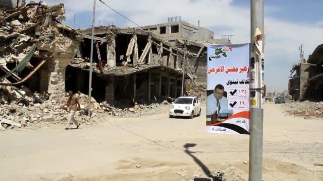 vídeos de stock, filmes e b-roll de en un muro de un colegio acribillado de balas de la ciudad vieja de mosul los carteles electorales prometen un futuro mejor para la segunda ciudad de... - irak