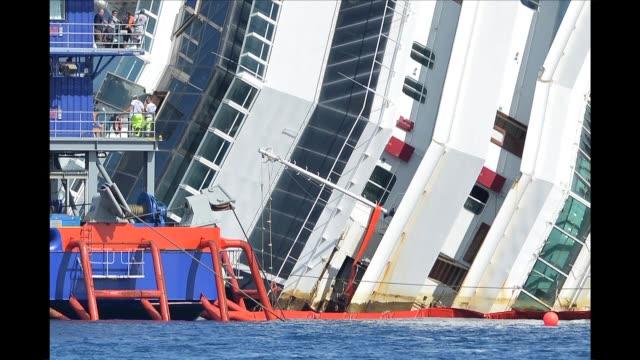 en una inedita operacion para enderezarlo, el crucero costa concordia, encallado desde hace 20 meses en la costa italiana, empezo a emerger del agua... - agua stock videos & royalty-free footage