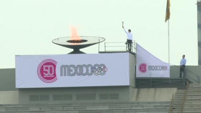 encendiendo el pebetero del estadio olimpico en la ciudad de mexico y con un desfile como hace 50 anos exatletas recordaron los juegos olimpicos de... - 1968 video stock e b–roll