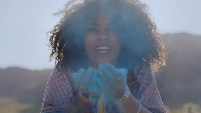 SLO MO. Enchanting young woman blows blue sand at camera and throws it in the air in Nevada desert.