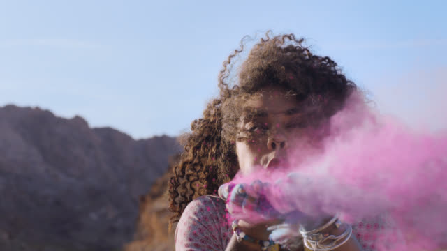 SLO MO. Enchanting young woman blows pink sand threw her fingers and smiles at camera in rocky desert landscape.