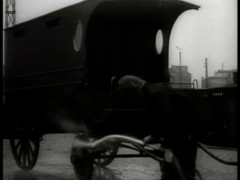 vidéos et rushes de enclosed wagon containing guillotine covered w/ tarp on rail car anatole deibler standing in rail yard w/ railroad employee assistant hosing off... - guillotine