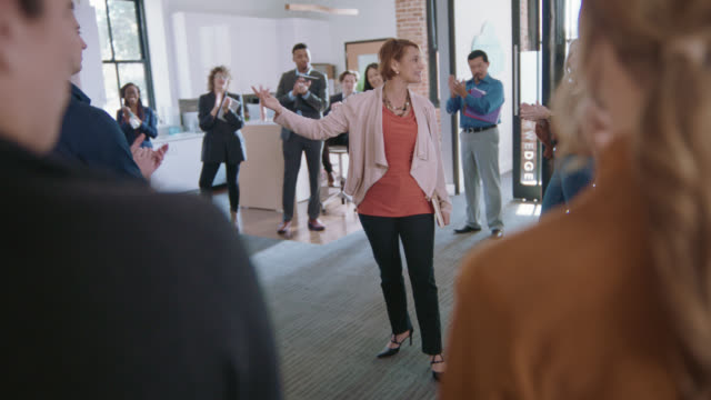 vídeos de stock, filmes e b-roll de encouraging businesswoman and her colleagues clap and congratulate two fellow employees during a team business meeting - latin american and hispanic ethnicity