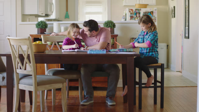 ws. encouraging father helps young daughters with homework after school. - homework stock videos & royalty-free footage
