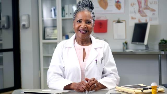 vidéos et rushes de encourageant ancien médecin femelle afro-américaine consulte le patient par vidéoconférence - doctoresse