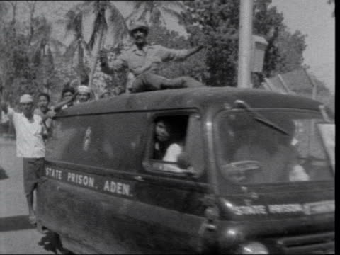 end of british rule in aden; aden: tawahi: pan lorry l-r with shouting and chanting arabs with flags, stops small open car along l-r with arabs in... - aden stock videos & royalty-free footage