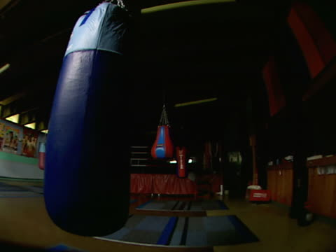 stockvideo's en b-roll-footage met end of empty boxing gym w/ hanging speed bags heavy bag posters decorate walls bg lights off - stootzak fitnessapparatuur