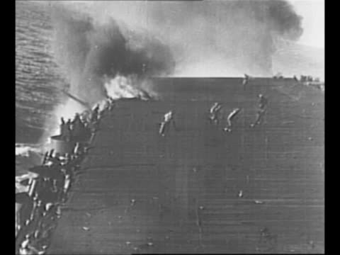 End of US aircraft carrier USS Yorktown burns after being hit by Japanese air fire during World War II Battle of Midway sailors scurry on deck / full...