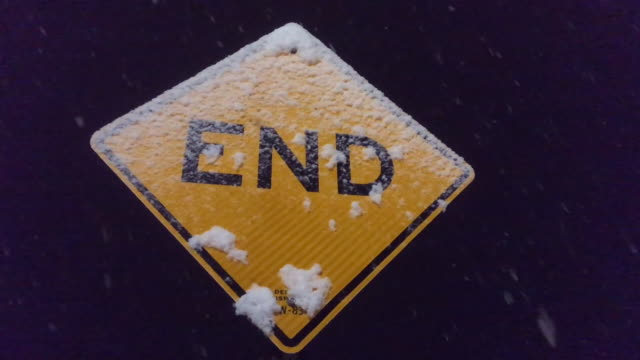 vídeos de stock e filmes b-roll de end sign at night with snow falling (close up) - the end