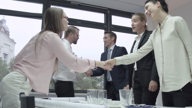 Ending of a business meeting in a conference room, business people shaking each other´s hands