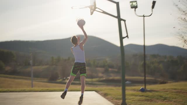 vidéos et rushes de energetic boy dribbles and shoots baskets alongside a scenic mountain range - mountain range