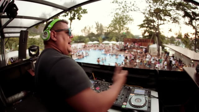 Energetic Brazilian DJ sings, dances, and waves hands in the air at exclusive Rio poolside club