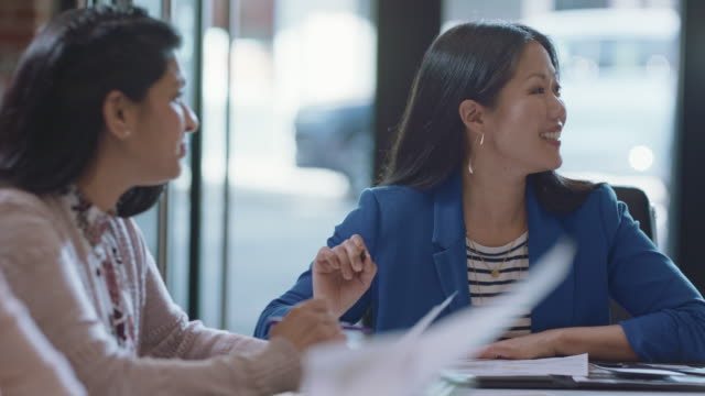 energetic diverse businesswomen brainstorm and discuss ideas during a team meeting in an office board room - brainstorming stock videos & royalty-free footage