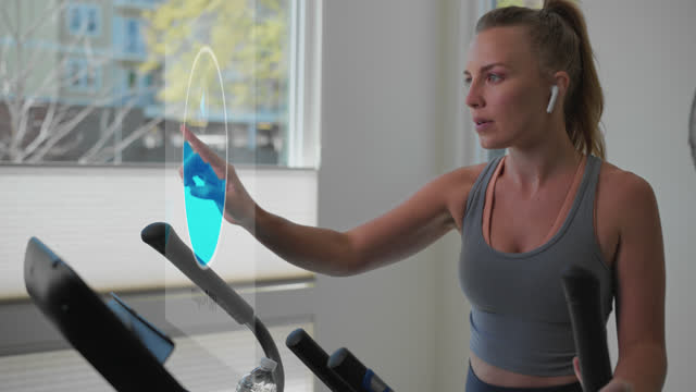 energetic woman chooses a workout from her elliptical machine - internet of things stock videos & royalty-free footage