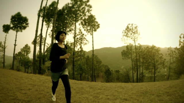 Energetic young woman walking and jogging in fresh air.